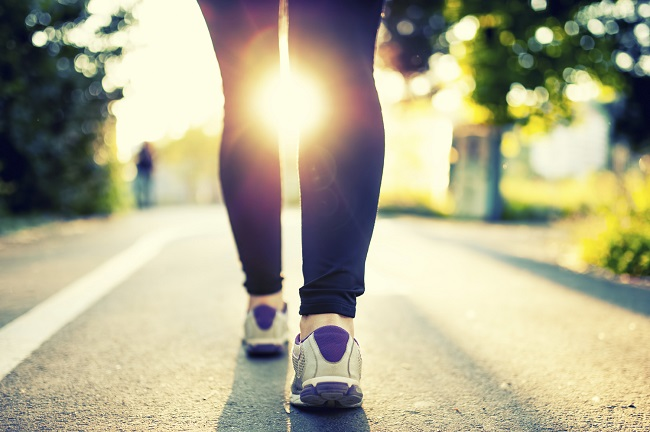 Close-up of woman athlete feet and shoes while running in park.